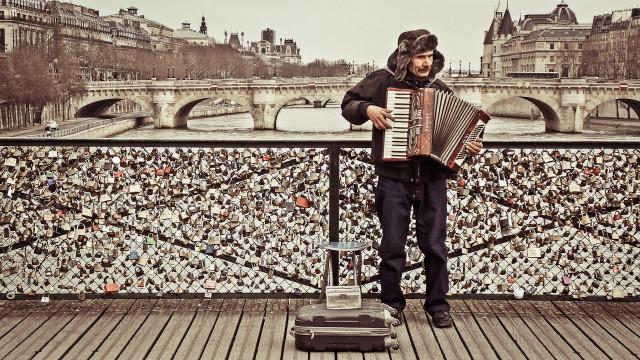 Аккордеонист на парижском мосту искусств на фоне тысяч замочков